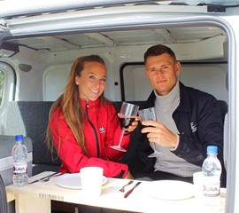two people drinking wine in the nissan nv200 camper van