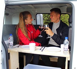two people drink wine in the back seat of the nv200 camper van
