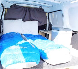a picture of the mattress and bedding in the nissan nv200 camper van
