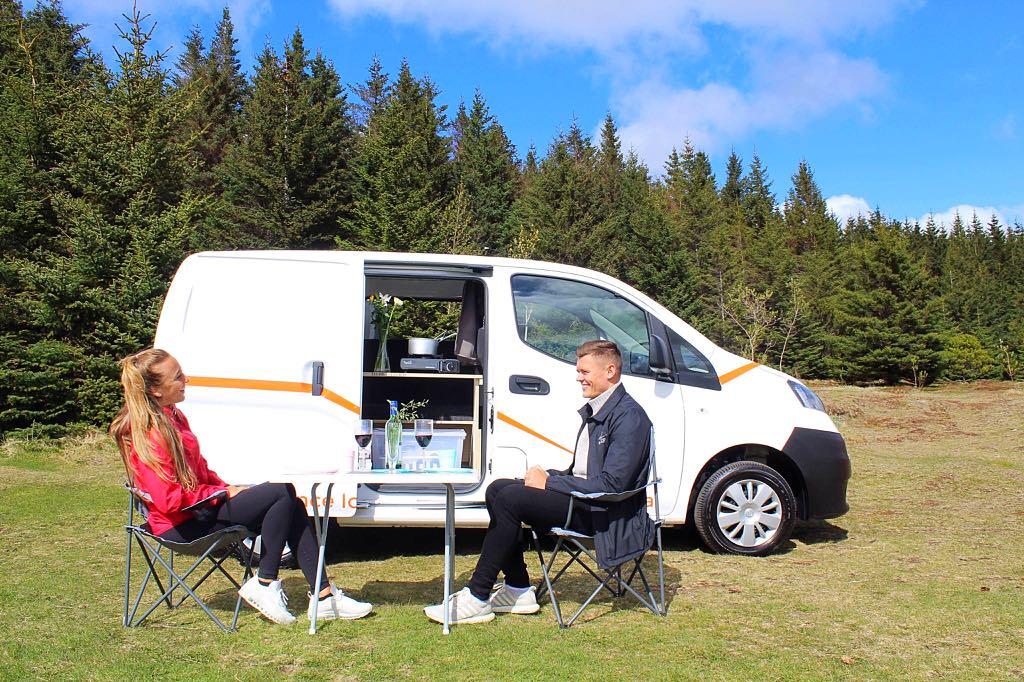 two people sit outside their nissan nv200 camper van rental