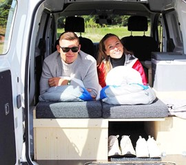 a man and a woman lay on the bed in the back of the nissan nv200
